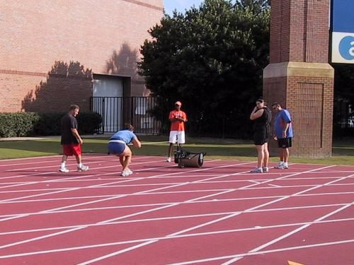 University of Florida - Power Pull Training - Coach O\'Neal ( the orange shirt ), A female shotputter in the black, and Coach Lemke the shotputter coach. This is a drill that they do to increase the thurst of the shotput throw. ( very high in resistance )
